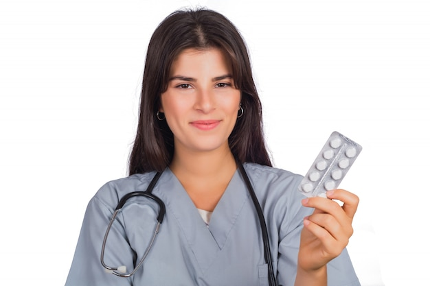 Female doctor with stethoscope and holding pills.