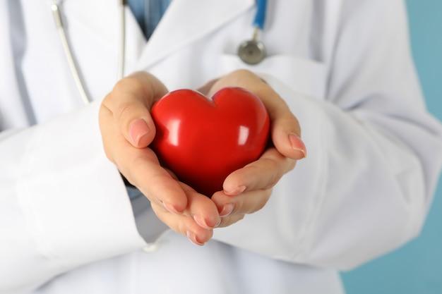 Женщина-врач со стетоскопом держит красное сердце