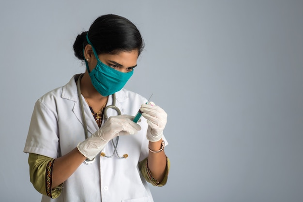 A female doctor with a stethoscope is holding and showing an injection or syringe.