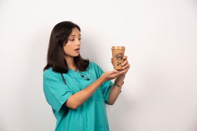 白い背景の上のコーヒーを見ている聴診器を持つ女性医師。