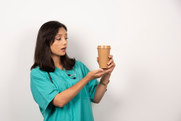 Medico donna con lo stetoscopio guardando il caffè su sfondo bianco. foto di alta qualità