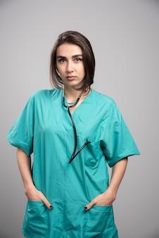 灰色の壁に聴診器が立っている女性医師。