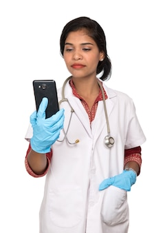Женщина-врач со стетоскопом разговаривает по мобильному телефону на белом фоне