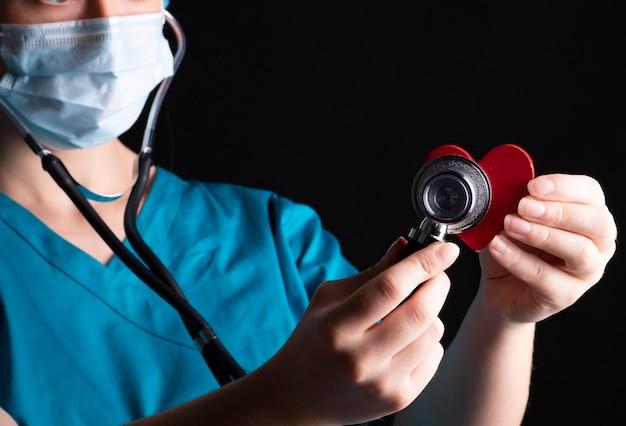 赤いハート、健康概念でそれを使用して聴診器で女医