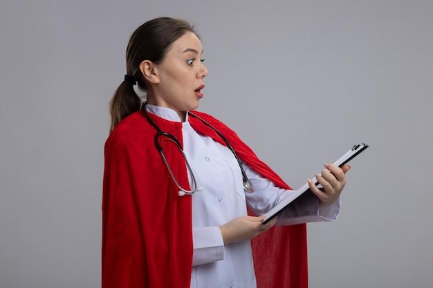 Dottoressa con stetoscopio in uniforme medica bianca e mantello da supereroe rosso che mostra appunti con pagine vuote guardando stupito e sorpreso in piedi sul muro bianco