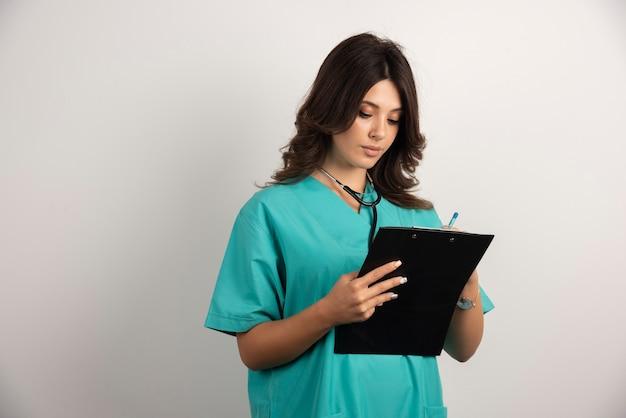クリップボードに聴診器を書いている女性医師。