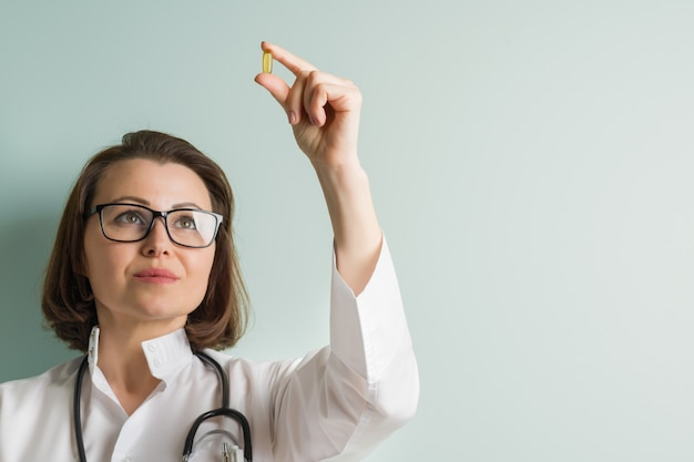 Female doctor with vitamin capsule.