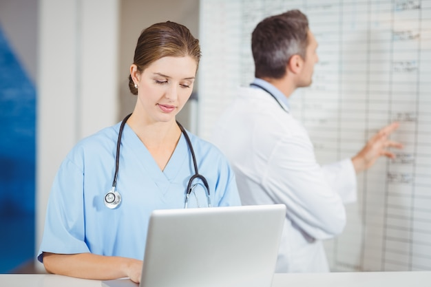 Female doctor working on laptop with colleague pointing at chart