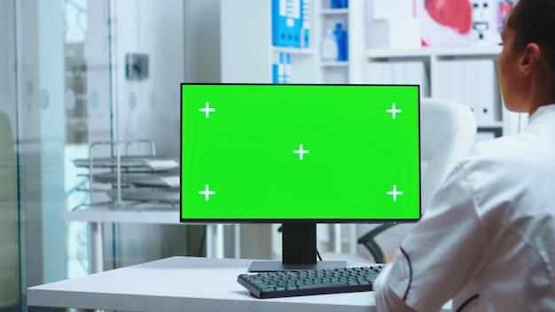 개인 클리닉 캐비닛에 녹색 화면이 있는 컴퓨터 작업을 하는 여성 의사. 유니폼을 입은 어시스턴트. 환자 진단을 확인하기 위해 클리닉 캐비닛에 크로마 키가 있는 모니터에서 작업하는 흰색 코트의 메딕.
