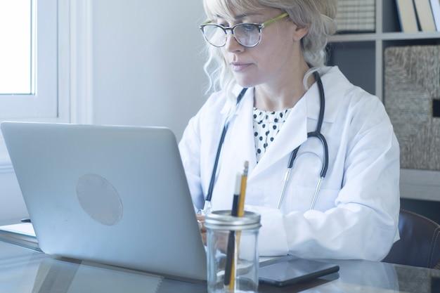 상담을 위해 노트북 작업을 하는 여성 의사. 홈 오피스에서 책상에 컴퓨터를 사용하는 백인 여자. 그녀의 노트북을 사용하여 환자의 상담을 위해 화상 통화에 참석하는 여성 최전선 직원