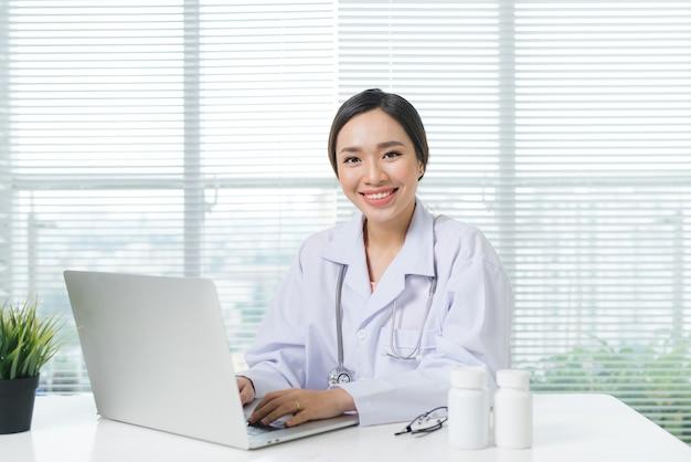 사무실 책상에서 노트북으로 일하고 웃는 여성 의사