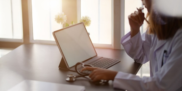 Female doctor working with tablet and writing on paperwork in office room