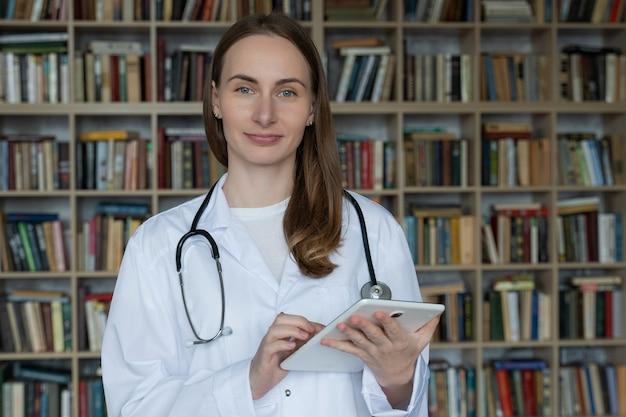 女性医師はラップトップを使用して、本棚との相談で薬に関するいくつかの情報を研究します