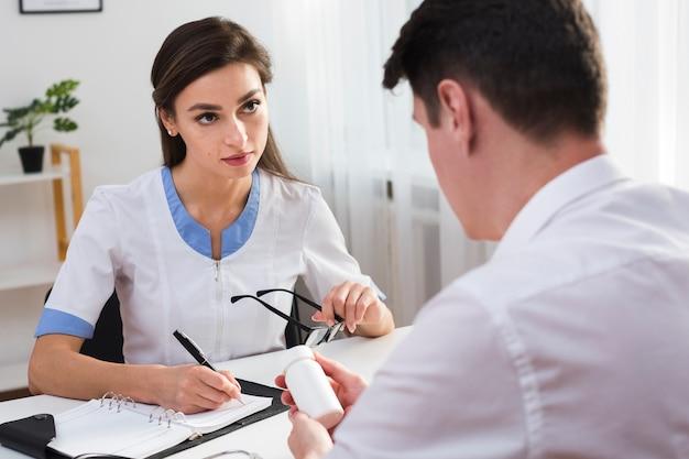 Женщина-врач пишет отчет и смотрит на пациента