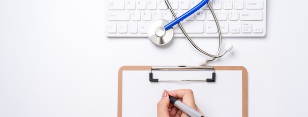 Female doctor writing a medical record case over clipboard on white working table with stethoscope, computer keyboard