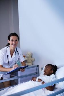 女医が患者が病院でベッドに横たわっている間クリップボードに書き込み