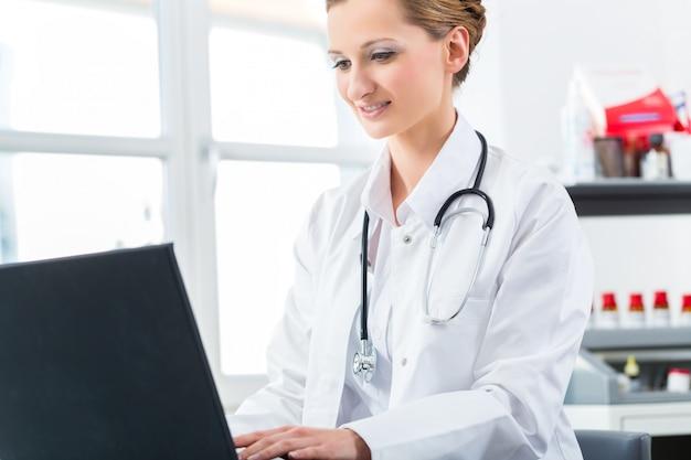 Женщина-врач пишет на пк в своей клинике