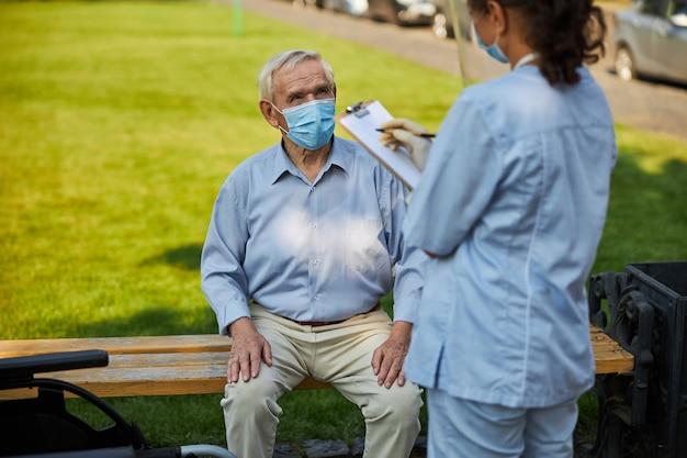 屋外の老人のための推奨事項を書く女性医師