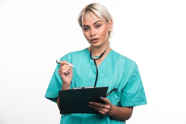 흰 벽에 펜으로 클립 보드에 뭔가 쓰는 여성 의사.