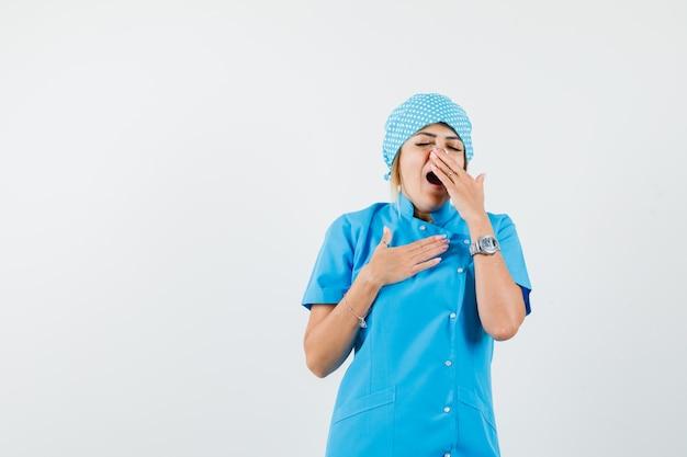 여성 의사가 파란색 유니폼을 입고 졸린 찾고