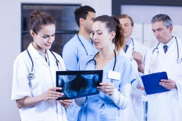 女性医師がレントゲン検査報告をチェックし、男性医師が後ろで議論している