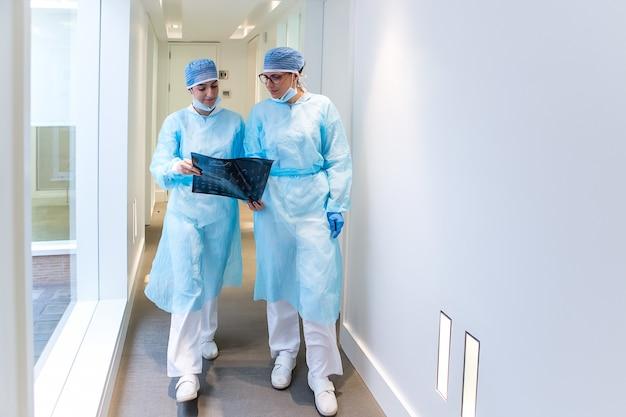 Female doctors examining x ray in clinic corridor