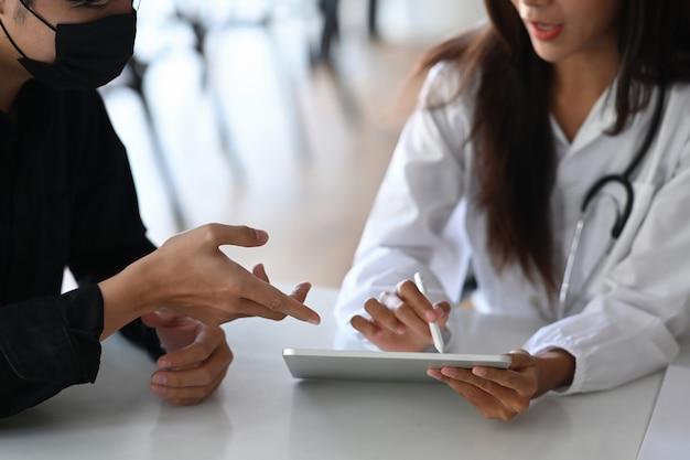 男性患者に治療を説明し、勧める女性医師。医療とヘルスケアの概念。
