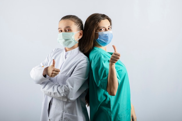 Female doctors in medical masks showing thumbs up