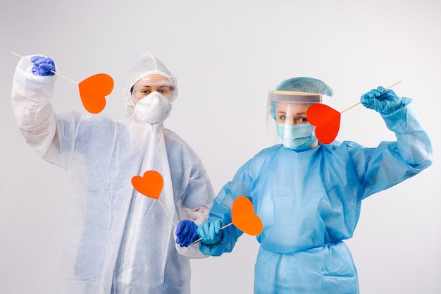 Female doctors in protective equipment hold red hearts on white isolated background