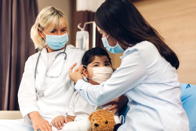 Женщина-врач в маске разговаривает с маленьким пациентом