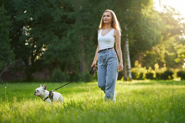 Female dog owner walking with french bulldog in park