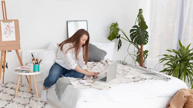 Женщина ведет видеоблог на своем ноутбуке