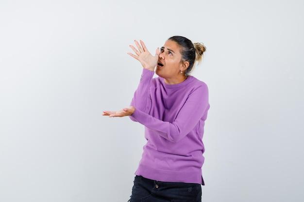 Женщина делает забавный жест рукой на носу в шерстяной блузке и выглядит сосредоточенной