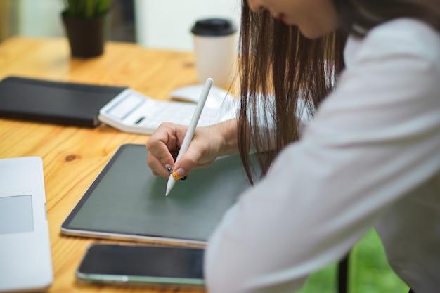 オフィスで木製のテーブルにスタイラスペンでタブレットに描く女性