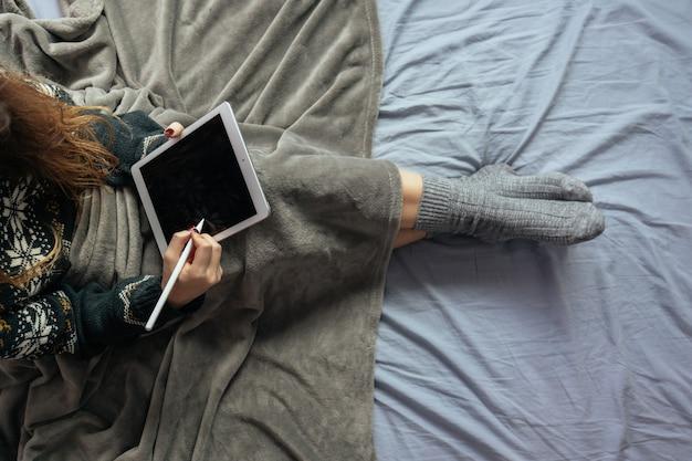 毛布で覆われたベッドに座っている間、タブレットの黒い画面に描く女性