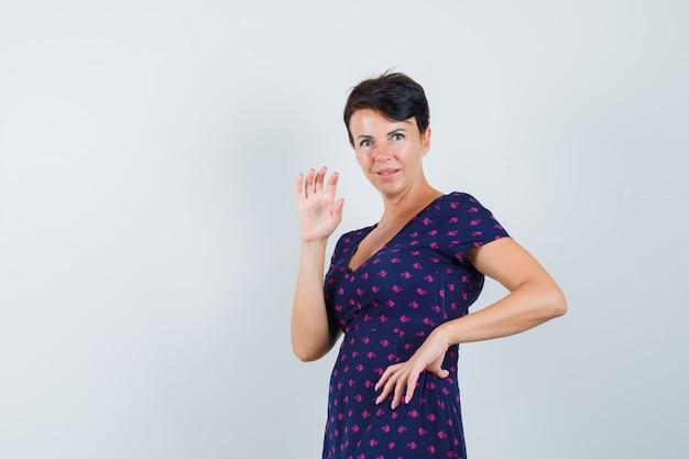 Donna in abito in posa mentre agita la mano e sembra carina, vista frontale.