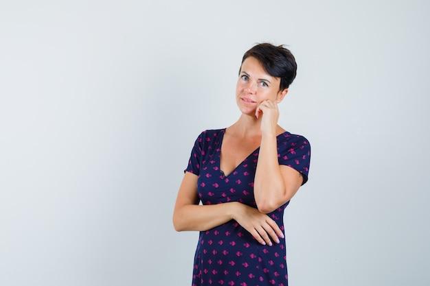 Donna in abito in piedi nella posa di pensiero e guardando sensibile, vista frontale.