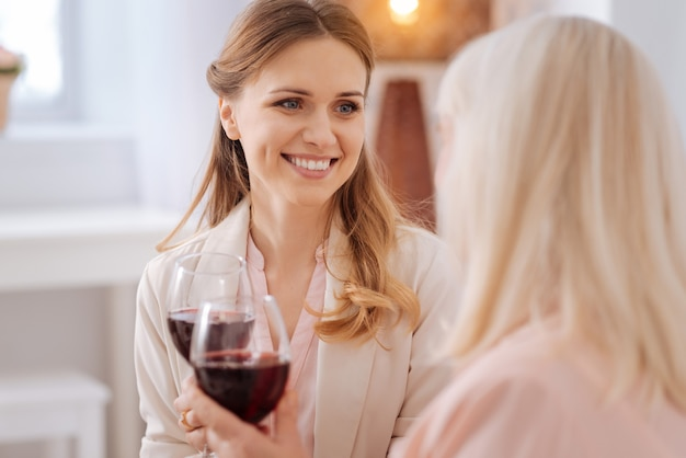 Female drink. happy nice beautiful woman smiling and looking at her mother while having wine with her