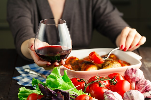 Female drink red wine and eating roiast chicken