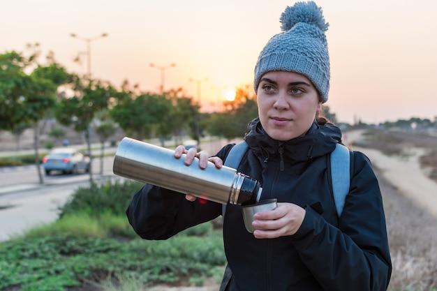 Женщина пьет горячий кофе. зимнее приключение. страсть к путешествиям. походы и путешествия