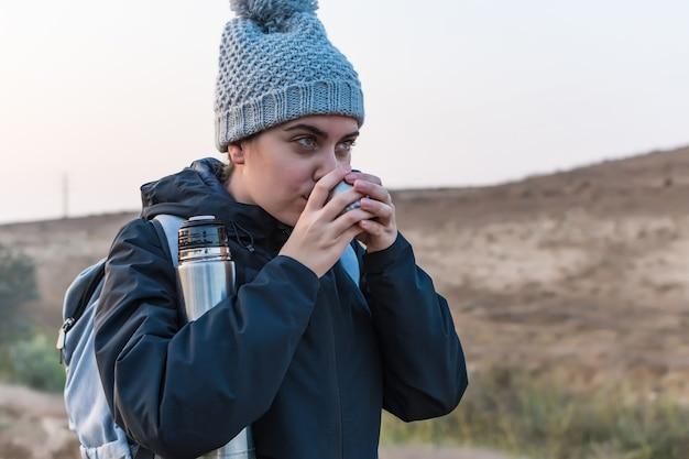 ホットコーヒーを飲む女性。冬の冒険。ワンダーラスト。ハイキングと旅行