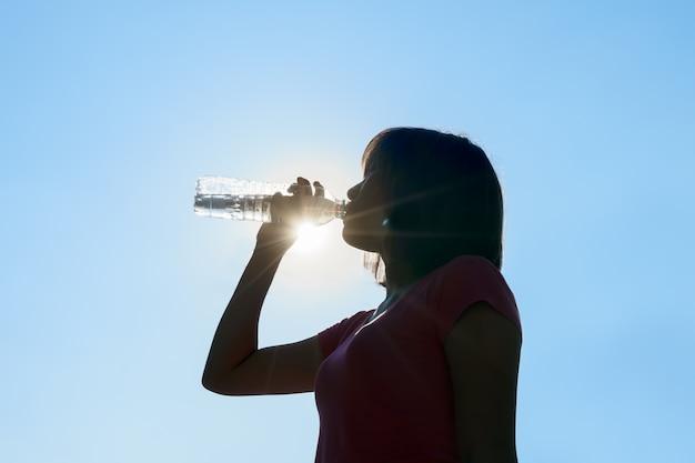 Female drinking water in hot summer - heat stroke concept.