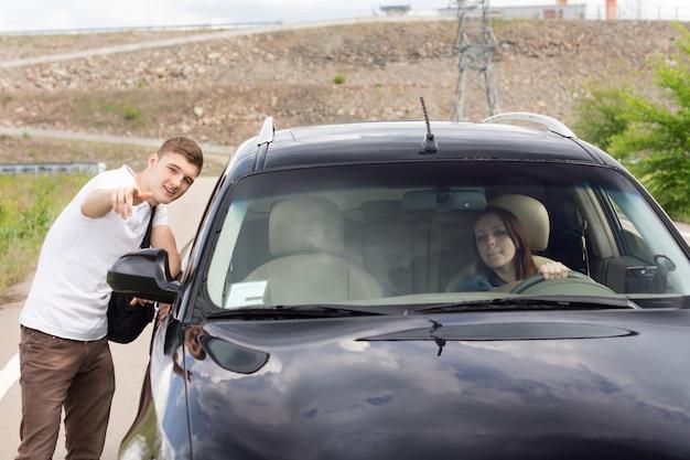 시골 길에서 그녀를 위해 길을 가리키는 길가에 서서 잘 생긴 젊은이에게 방향을 묻는 여성 운전자