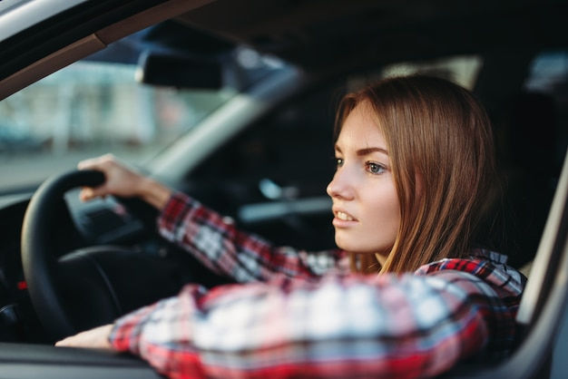 Female driver beginner looks out of the car window