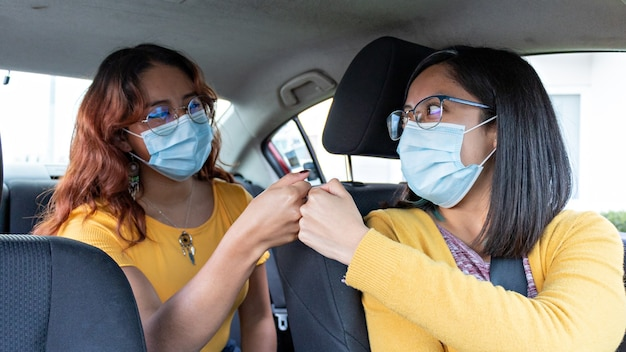 The female driver of a car safely greets the female passenger in the back seat, both wearing face masks