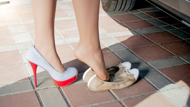 여성 운전자는 차를 운전하기 전에 불편한 신발을 발레 플랫으로 갈아 입습니다.