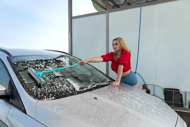 흰색 거품에 텔레스코픽 세척 브러시로 차를 청소하는 여성 운전자