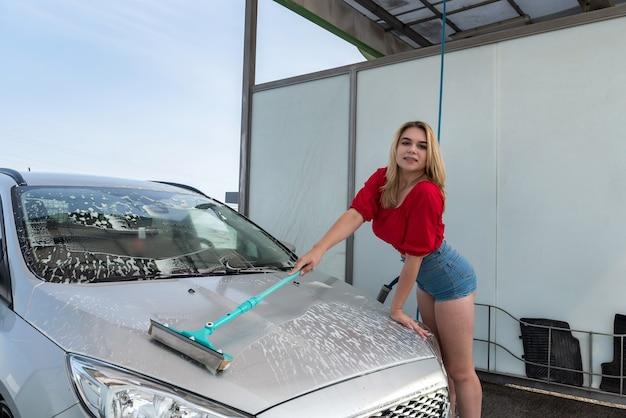 白い泡の伸縮自在の洗浄ブラシで彼女の車を掃除する女性ドライバー