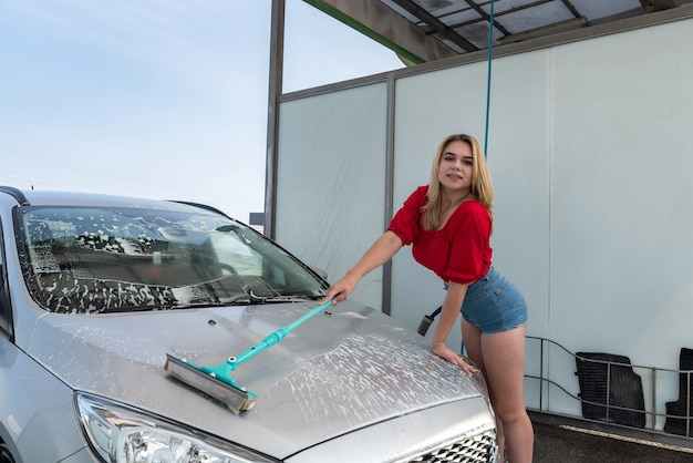 Female driver cleaning her car with telescopic washing brush in white foam