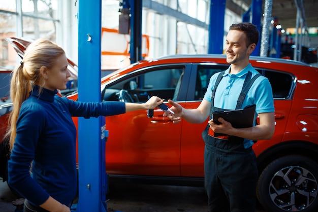 여성 운전자는 유니폼, 자동차 서비스 스테이션에서 작업자에게 키를 제공합니다. 자동차 점검 및 검사, 전문 진단 및 수리